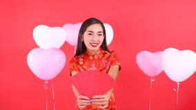 Woman in Qipao chinese dress. Holding red pocket momey isolated on red background stock video footage
