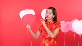 Woman in Qipao chinese dress. Holding red pocket money isolated on red background stock video