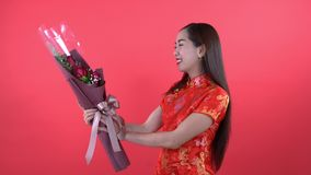 Woman in chinese dress with balloon. Woman in qipao chinese dress holding roses isolated on red background stock video