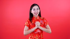 Woman in qipao chinese dress. Isolated on red background stock footage
