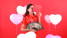 Woman in Qipao chinese dress. With fan and red heart shape and balloon isolated on red background stock footage
