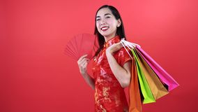 Woman in Qipao chinese dress. Holding money in red chinese pocket and shopping bag isolated on red background stock video