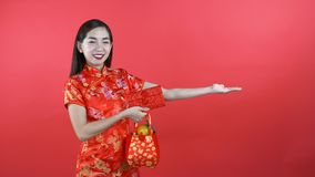 Woman in Qipao chinese dress. Holding red pocket money isolated on red background stock footage