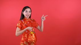 Woman in Qipao chinese dress. Holding red pocket money isolated on red background stock video footage