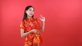 Woman in Qipao chinese dress. Holding red pocket money and orange bag pointing to copyspace isolated on red background stock video