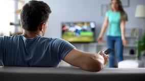 Woman quarreling, man watching football match, ignoring conflict, relationship