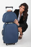 Woman quatting with suitcase Stock Photos