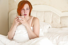 Woman in Queen Size Vintage Bed drinking Morning Coffee. White Cup white Blanket warm tone background royalty free stock photography