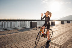 Woman quenches thirst while riding a bike Royalty Free Stock Images