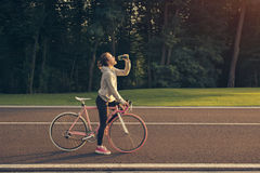 Woman quenches thirst after riding a bike Royalty Free Stock Photography