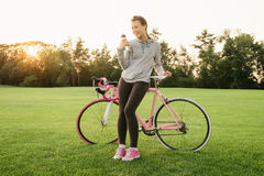 Woman quenches thirst after riding a bike Stock Photography