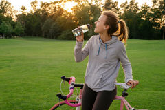 Woman quenches thirst after riding a bike Royalty Free Stock Photos