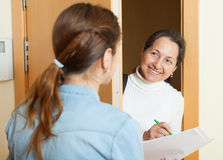 Woman questionnaire for  mature social worker. Or employee of the company at door Royalty Free Stock Photo