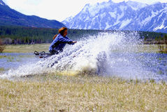 Woman racing ATV. Woman driving an ATV through a marshy landscape with snowy mountains in the background stock image