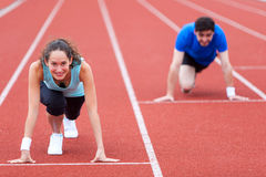 Woman racing with a man at the stadium Stock Photography