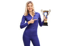 Woman in a racing suit holding a trophy. Young woman in a blue racing suit holding a trophy and pointing towards it isolated on white background stock photos