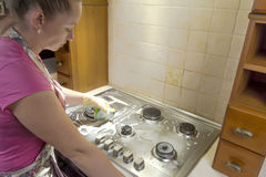 Woman with a rag cleans a gas stove. stock image