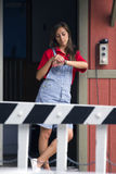 Woman and railroad crossing. Attractive young woman checking watch with railway or railroad crossing barrier in foreground stock images