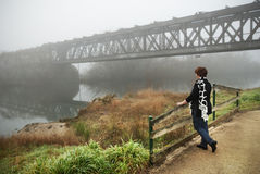 Woman with railway bridge and fog Stock Image