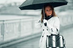Fashion woman with umbrella walking in the rain on city street Royalty Free Stock Photos