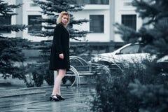 Fashion woman in black coat walking on city street Stock Photography