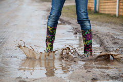 Woman with rain boots jumps Stock Photo