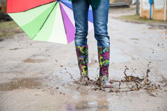 Woman with rain boots jumps Stock Photos
