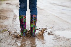 Woman with rain boots jumps Stock Images