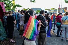 Woman with rainbow flag in crowd gives peace sign to passing motorists Stock Image