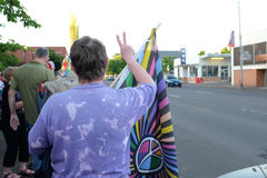 Woman with rainbow flag in crowd gives peace sign to passing motorists Stock Photography