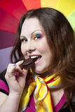 Woman with rainbow make up eating cookie. Beautiful woman with freckles, creative rainbow make-up and nails biting chocolate cookie at rainbow background stock image