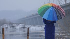 Woman with rainbow umbrella during snowfall. Foggy gloomy back view winter shot of woman holding rainbow umbrella, standing near the bridge in the city during stock video