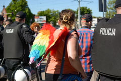 Woman with rainbow wings standing among policemen. Royalty Free Stock Images
