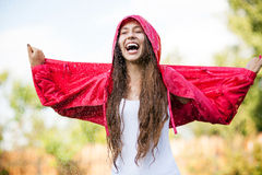 Woman in raincoat enjoying the rain Royalty Free Stock Image