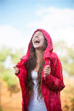 Woman in raincoat enjoying the rain Stock Images