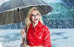 Woman in raincoat  holds umbrella Stock Photo