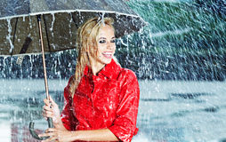 Woman in raincoat  holds umbrella Stock Images