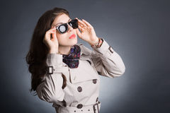 Woman in the raincoat and sunglasses Stock Photography