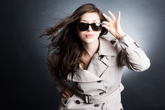 Woman in the raincoat and sunglasses Royalty Free Stock Photos