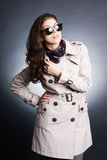 Woman in the raincoat and sunglasses Stock Images
