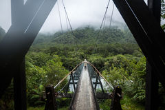Woman in Raincoat walking on Suspended bridge Stock Images