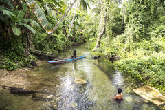 Woman in rainforest creek, man in canoe, West Papua Royalty Free Stock Image