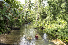Woman in rainforest creek, West Papua Royalty Free Stock Image