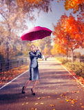 Woman while raining on the autumn street Stock Photo