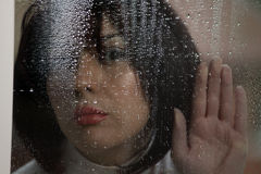 Woman at rainy window Stock Photos