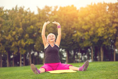 Woman with raised arms sitting. Lady with closed eyes outdoor. Concentrate and breathe deeply. Flexibility and health Royalty Free Stock Photo