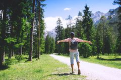 Woman with raised arms up on nature in Dolomites, South Tyrol, Italy, Europe. Hiker woman with raised arms up on nature outdoors, back view. Travel at Dolomites royalty free stock images