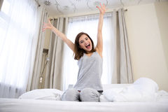 Woman with raised hads up on the bed Stock Photo