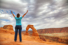 Woman with raised hands in front of Delicate Arch Royalty Free Stock Photo