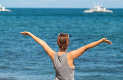 Woman with raised hands on the sea background. Happy girl in casual look on the seaside. stock images